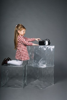 Side view of a girl kneeling on transparent cubes holding virtual reality glasses against gray background