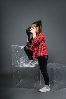 Side view of a girl photographing with camera standing near the blocks