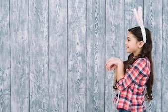 灰色の木製の背景の前にウサギのようにポーズをとる女の子の側面図