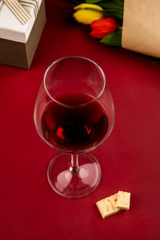 Вид сбоку бокал вина с белым шоколадом и букет красных и желтых цветных тюльпанов на красном столе