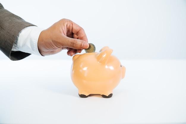 白い背景と非常に良い光でセラミック貯金箱にコインを置く手の側面図