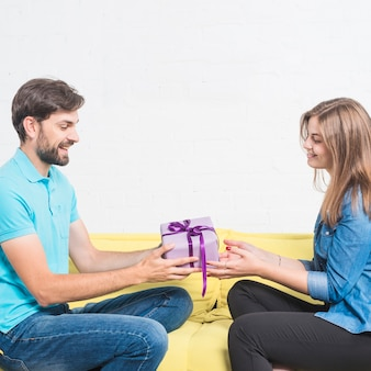 Side view of a happy man sitting on sofa giving valentine gift to his girlfriend