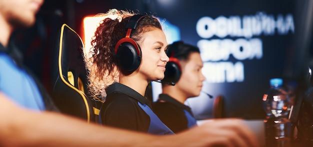 Вид сбоку на счастливую девушку-киберспортсменку из смешанной расы в наушниках, играющую онлайн