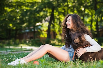 Side view of a happy young woman sitting with her dog in garden