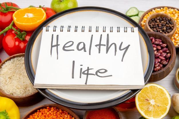 白い表面でベジタリアンディナー料理のための新鮮な野菜のコレクションの白い鍋にスパイラルノートの健康的な生活の碑文の側面図