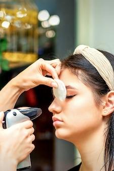 미용실에서 여성 얼굴에 에어브러시 메이크업 기초를 만드는 에어로그래프를 사용하는 메이크업 아티스트의 측면.