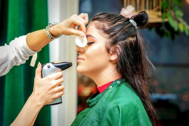 女性の顔にエアブラシのメイクアップファンデーションを作るエアログラフを使用してメイクアップアーティストの側面図