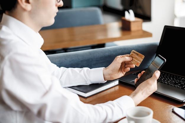 コーヒーショップの机に座っているスマートフォンとクレジットカードを使用して男性の手の側面図。