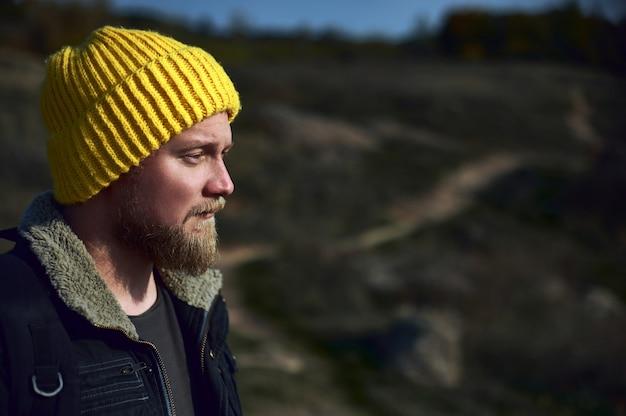 Вид сбоку мужчины-туриста в желтой шерстяной шляпе над дорожкой в горах. портрет крупным планом. концепция приключений.