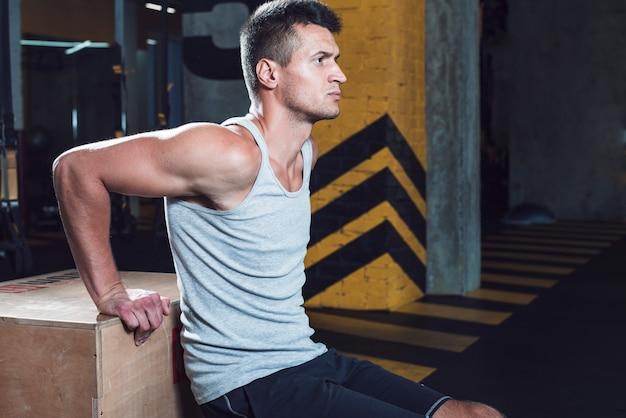 フィットネスクラブでトレーニングをしている男の側面図