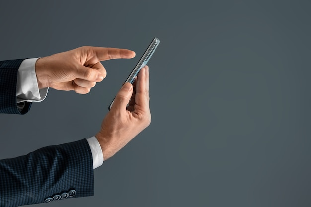 남자의 손의 측면보기 스마트 폰에 손가락을 누르면
