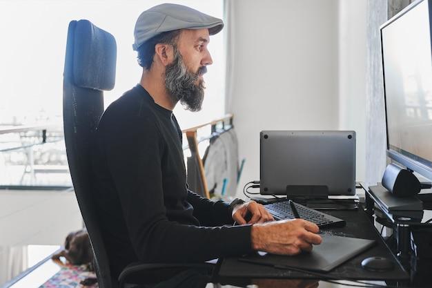 랩톱, 외부 모니터로 집에서 일하고 그래픽 태블릿을 사용하는 남자의 측면보기