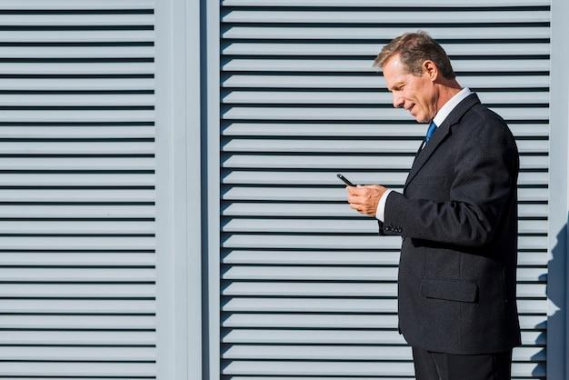 Взгляд со стороны зрелого бизнесмена используя мобильный телефон