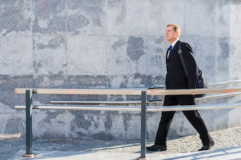 Side view of a mature man walking near railing