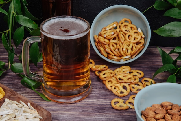 Вид сбоку кружка пива с мини-крендели на деревенском