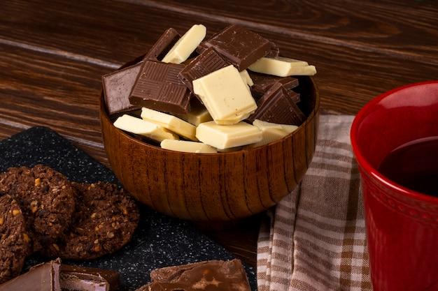 ティーオートミールクッキーと素朴な背景に木製のボウルに暗いと白いチョコレートの部分とマグカップの側面図