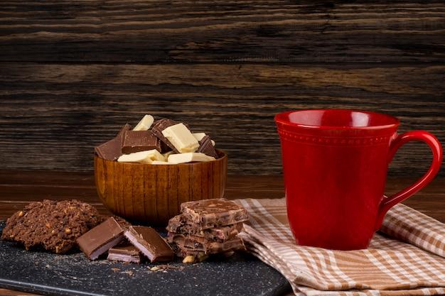 素朴な背景にマグカップティーオートミールクッキーとダークとホワイトのチョコレートの部分の側面図