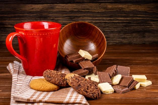 ティーオートミールクッキーと素朴な背景に木製のボウルから散在している暗くおよび白いチョコレート部分とマグカップの側面図