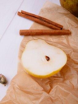 Вид сбоку ломтик груши с палочки корицы на коричневой пергаментной бумаге на белом фоне деревянные