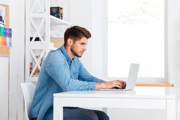 Вид сбоку задумчивого красивого бородатого случайного бизнесмена, сидящего с ноутбуком в офисе