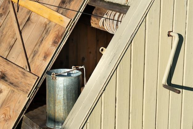 開いたドアと水の金属製のバケツばかとロシアの伝統的なドローウェルの側面図