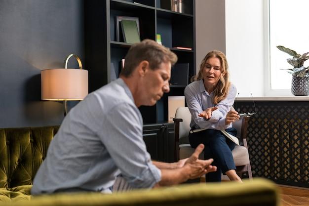 彼と話している金髪の女性の隣にソファに座って考えている悲しい深刻な中年男性の側面図