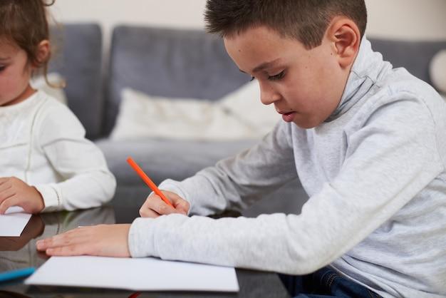 Вид сбоку на школьника в серой рубашке, сосредоточенный на рисовании цветным карандашом. цветные деревянные карандаши, лежащие на столе.