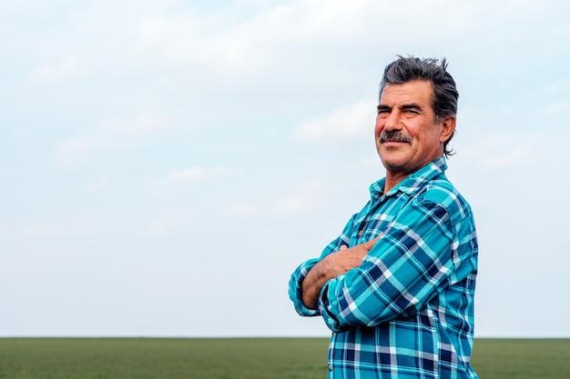 Вид сбоку старшего фермера со скрещенными руками, стоя в поле, исследующем урожай.