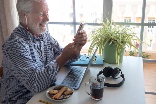 ラップトップで作業しているひげを持つ年配の男性の側面図。手に携帯電話。白い机。窓からの明るい光