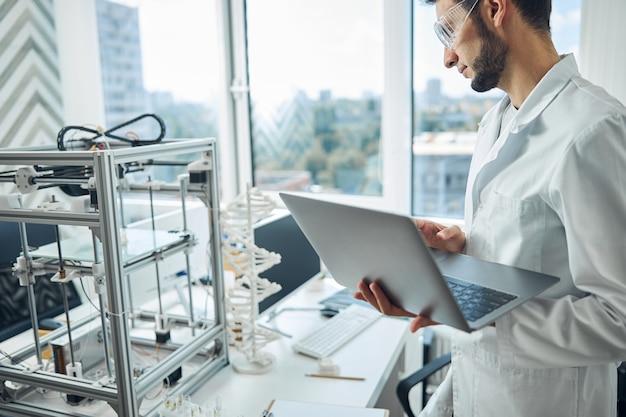 3 차원 물체를 인쇄하는 장치를 응시하는 심각한 남성 과학자의 측면보기