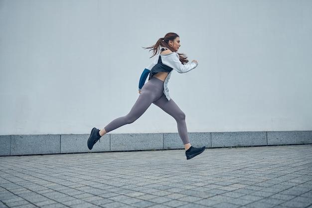 Вид сбоку серьезной сильной длинноволосой спортсменки в кроссовках, бегущей у стены на открытом воздухе