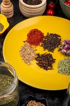 黄色のプレートに一連のスパイスとハーブのペッパーコーンアニス種子クローブ赤唐辛子フレークとティーのバラのつぼみの側面図