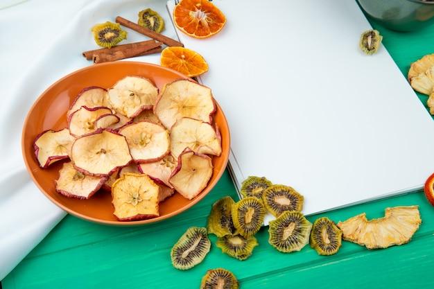 Вид сбоку альбом с сушеными яблочными чипсами на тарелку на белом и зеленом фоне