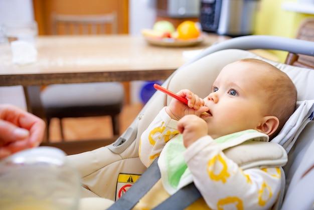 어린이 좌석에 앉아 장난감을 조금씩 먹는 똑똑한 어린 소녀 유아의 측면보기