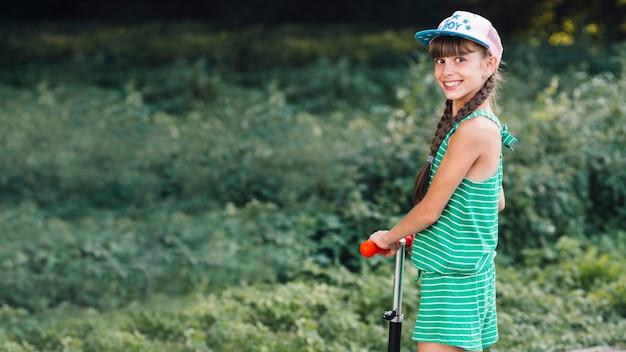 킥 스쿠터에 모자 서 입고 웃는 여자의 모습