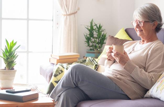 커피잔을 들고 집에서 소파에 앉아 웃고 있는 노년 여성의 옆모습
