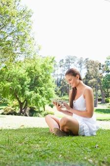 Вид сбоку улыбается женщина на газоне с планшетным компьютером