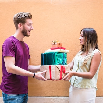 Side view of a smiling young couple holding stack of gifts