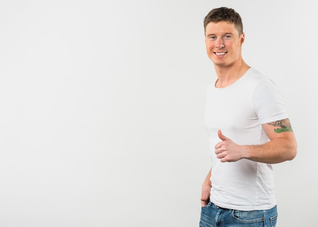 Вид сбоку улыбающегося молодого человека, показывая большой палец вверх знак на белом фоне