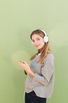 Взгляд со стороны усмехаясь музыки молодой женщины слушая на наушниках против зеленой предпосылки