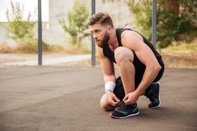 스포츠맨 운동선수의 옆모습은 야외에서 그의 신발끈을 묶는다
