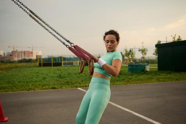 スポーツ分野で屋外クロストレーニングを実行しながらサスペンションストラップで腕の運動をしているスポーティな決定的な中年のアフリカ系アメリカ人、混血の女性の側面図