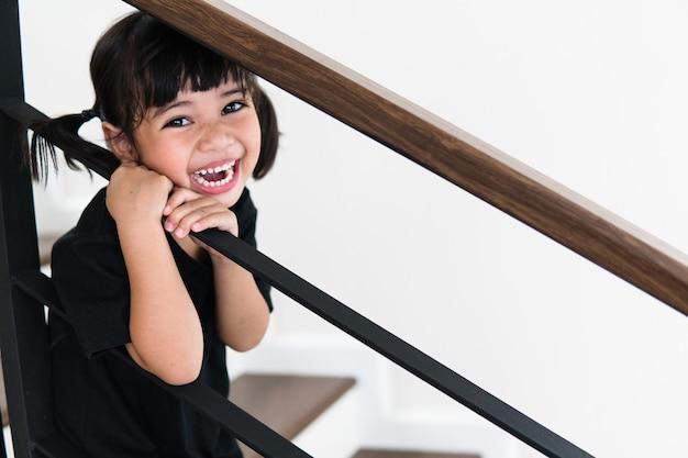 집에서 계단의 측면 보기입니다. 계단을 오르는 어린 소녀가 있습니다.