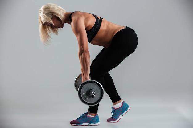 Вид сбоку сильной сосредоточенной мускулистой взрослой спортсменки