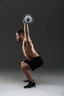 Вид сбоку сильного мускулистого культуриста