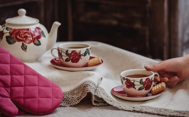 テーブルクロスの上のティーポットとクッキーとティーカップとバラの花柄のお茶セットの側面図