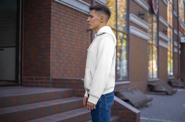 れんが造りの建物を背景に若い男に白いパーカーのプレゼンテーションの側面図。店内広告用のカジュアルウェアのモックアップ。あなたのパターンとデザインのための服のテンプレート。
