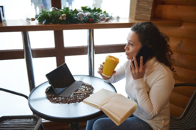 Вид сбоку женщины, пьющей вкусный напиток во время разговора по мобильному телефону, сидя у окна в кафетерии