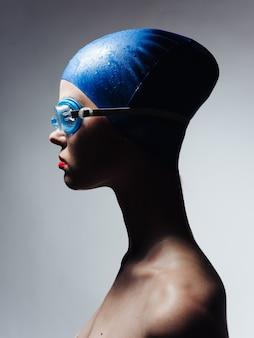 青い水泳帽と灰色の背景のメガネの女性の側面図