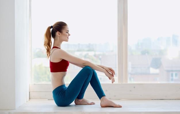 창턱과 빨간 티셔츠 요가 피트니스에 앉아 파란색 레깅스에 여자의 측면보기.